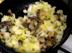 Добавляем грибы к луку, перемешиваем и обжариваем