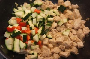 Добавляем овощи в сковороду к куриному филе