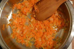 добавляем тертую морковь, смешиваем с луком и обжариваем